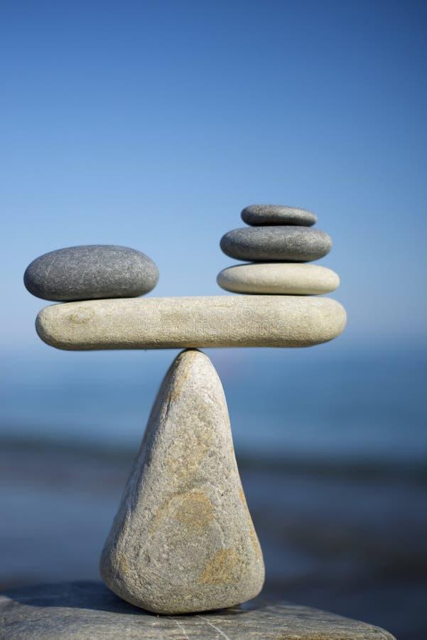Het in evenwicht brengen van zwart-witte kiezelstenen op de bovenkant van steen Het symbool van schalen wordt gemaakt van stenen royalty-vrije stock afbeelding