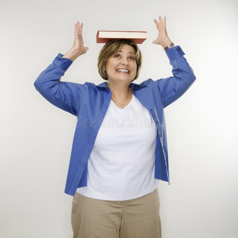 Het in evenwicht brengende boek van de vrouw op hoofd. royalty-vrije stock foto's