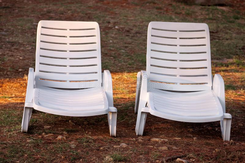 Het exotische strand op Middellandse Zee, wit plastiek sunbeds voor het zonnebaden en ontspant op gras in tropische tuin van toev royalty-vrije stock foto