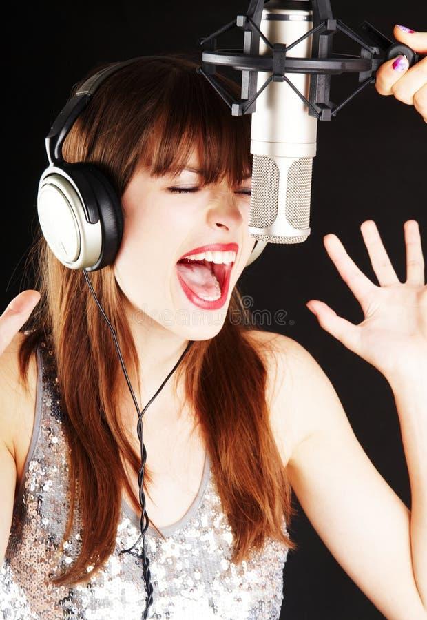 Het expressieve meisje zingen aan de microfoon stock fotografie