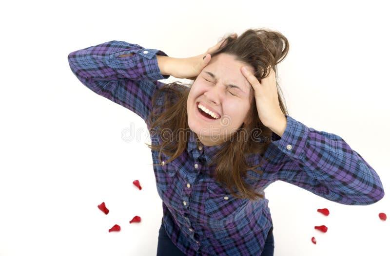Het expressieve portret van een mooi meisje die met haar handen aan haar oren, studio schoot op wit gillen stock foto's