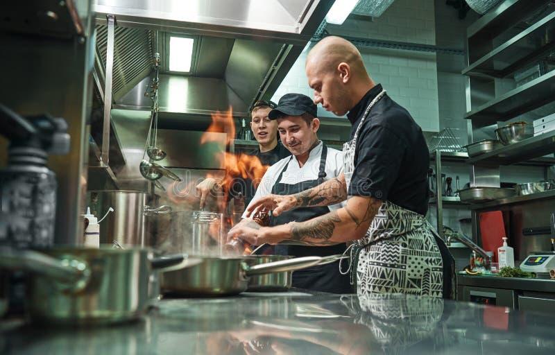 Het extreme Koken Profesionalchef-kok die zijn twee jonge stagiairs veilig onderwijzen hoe hoe te flambe voedsel Restaurantkeuken stock afbeelding