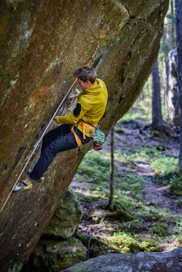 Het extreme sport beklimmen De klimmer die van de rots zich aan een klip vastklampt Openlucht levensstijl Scandin stock afbeelding