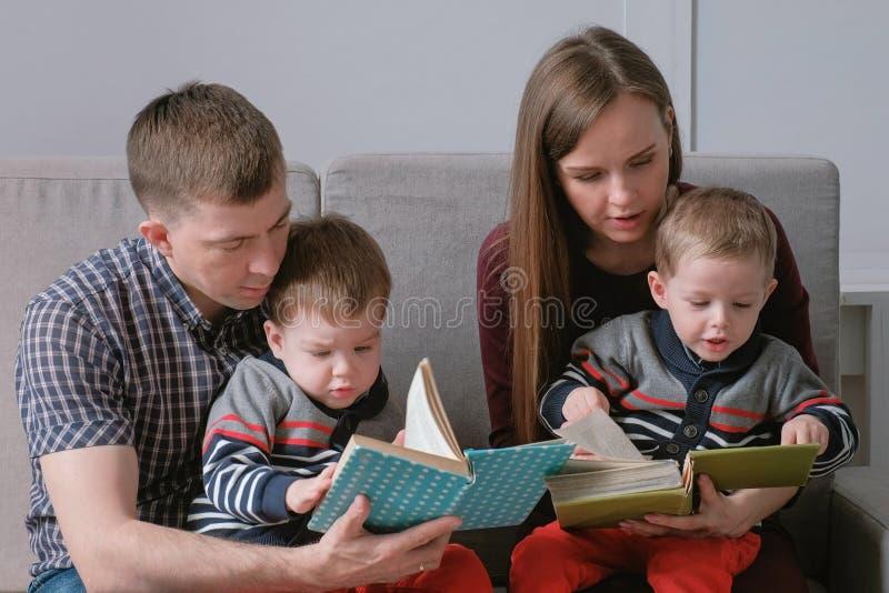 Het familiemamma, de papa en twee tweelingbroers lezen boeken zittend op de bank De tijd van de familielezing royalty-vrije stock afbeelding