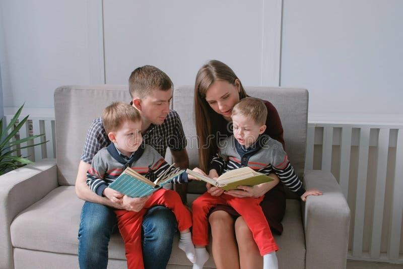 Het familiemamma, de papa en twee tweelingbroers lezen boeken zittend op de bank De tijd van de familielezing royalty-vrije stock foto