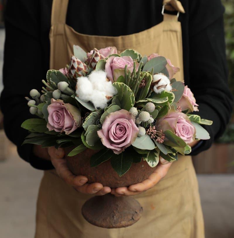 Het feestelijke bloemstuk van palevioletrozen en katoen bloeit in de holding van de vaasbloemist bij de bloemenboutique royalty-vrije stock fotografie