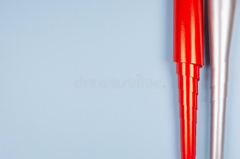 Het feestelijke malplaatje voor ontwerp en tekst van helder glanzend rood en metaal zilveren verpakkend document rolt op pastelkl stock fotografie