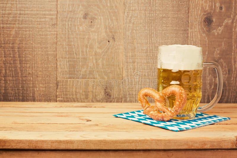 Het festivalachtergrond van het Oktoberfest Duitse bier met bierglas en pretzel op houten lijst royalty-vrije stock foto