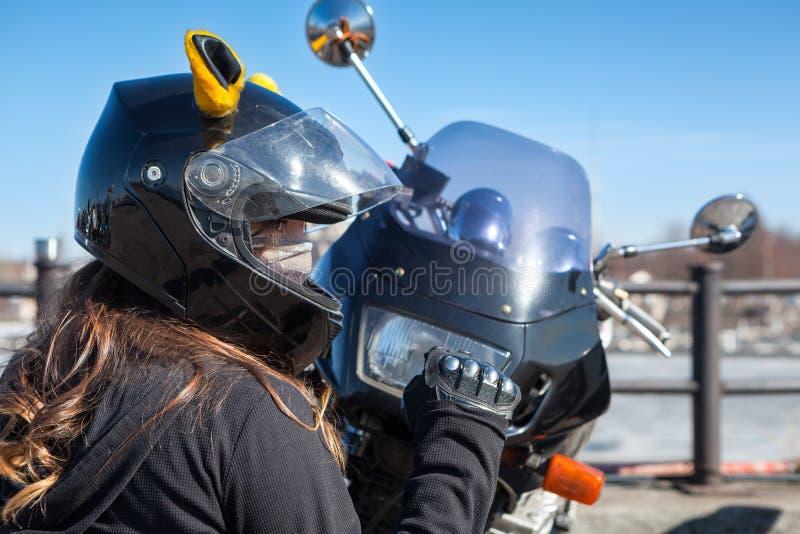 Het fietsermeisje in helm met masker klemt vuist dicht terwijl het zitten voor plastic voorkap met koplamp van haar motorfiets royalty-vrije stock foto's