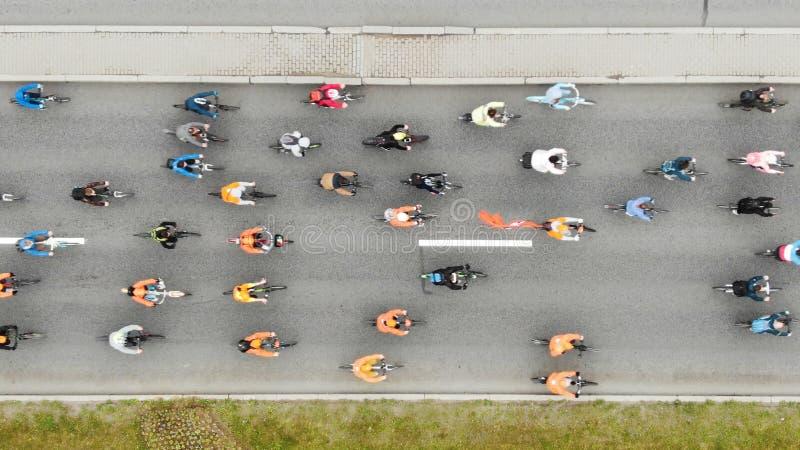 Het fietserspedaal en concurreert langs brede asfaltweg stock fotografie