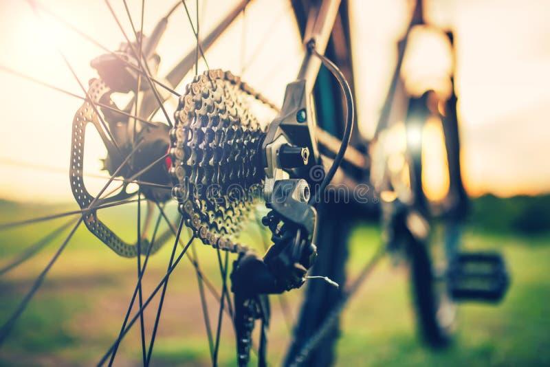 Het fietswiel met de details van de toestelhefboom, ketting en spokes, past mechanisme aan stock afbeelding