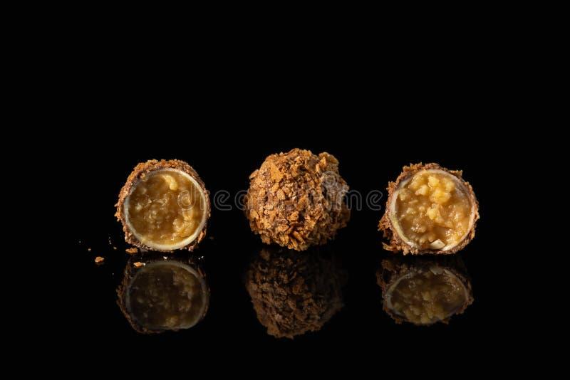 Het fijne chocoladesuikergoed met kaaskaramel het vullen op zwarte achtergrond met bezinning, sluit omhoog stock fotografie