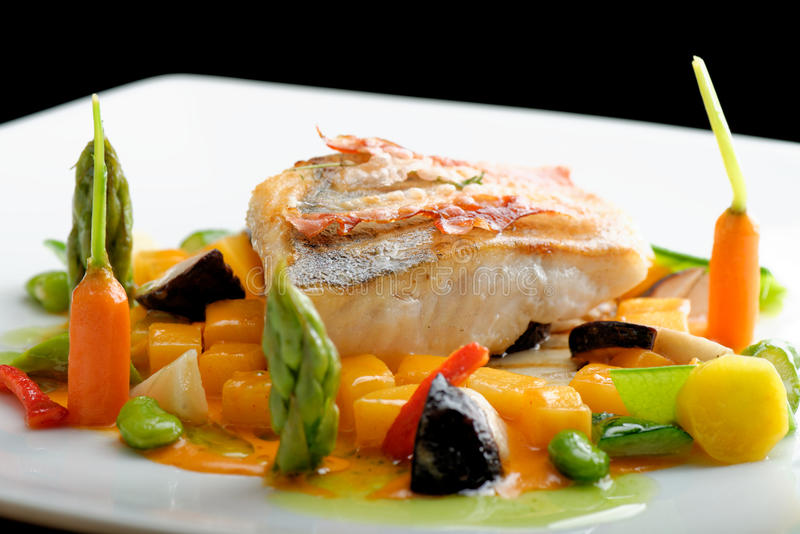 Het fijne dineren, Wit visfilet gepaneerd in kruiden en kruid met geroosterd bacon royalty-vrije stock afbeeldingen