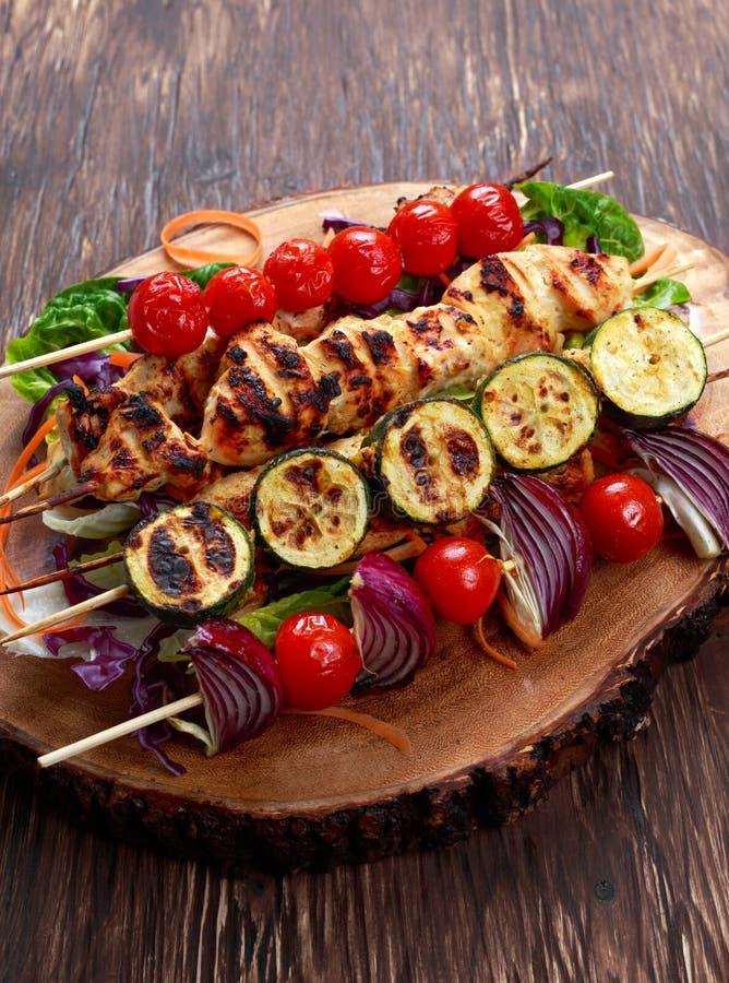 Het filethaakwerkkebab van de braadstukkip met kers op BBQ wordt geroosterd die tomaten, courgette en rode uien op bamboestokken stock fotografie