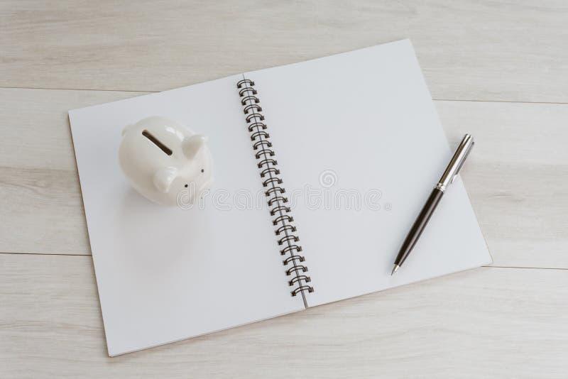 Het financiële, investeringsplan, de begroting of het besparingsdoel maken van een lijst, pening wit leeg document notaboek met p stock foto's