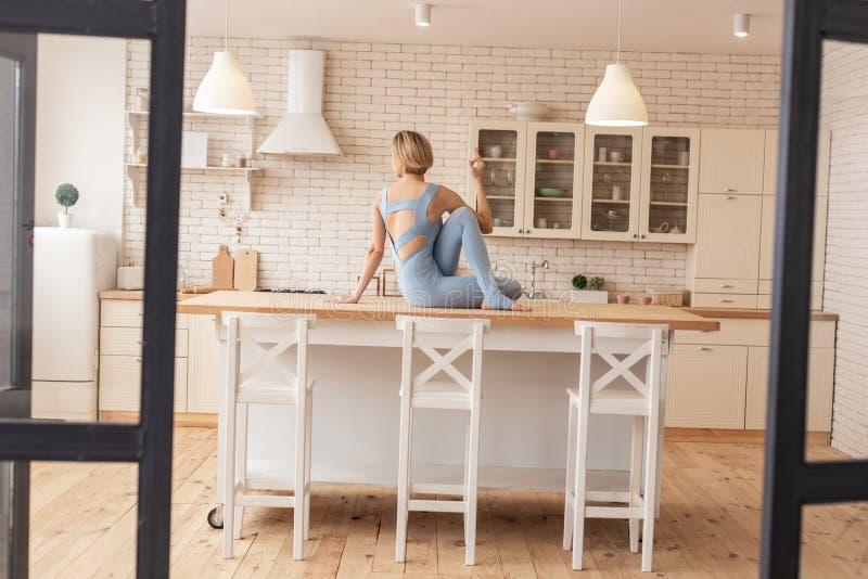 Het flexibele resolute jonge meisje ongebruikelijk samenstellen stelt op keuken het werk oppervlakte royalty-vrije stock afbeeldingen