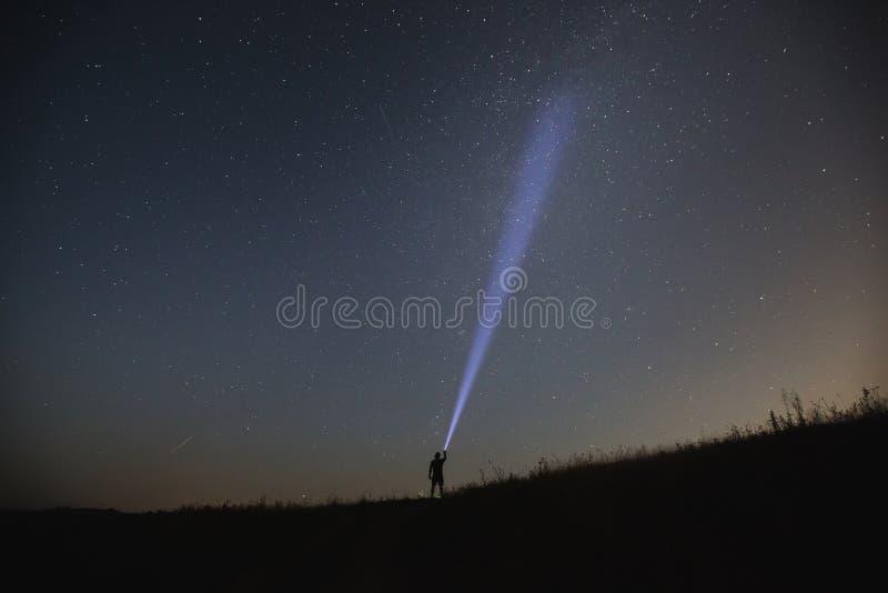 Het flitslicht van het mensenpunt aan de nachthemel stock afbeeldingen