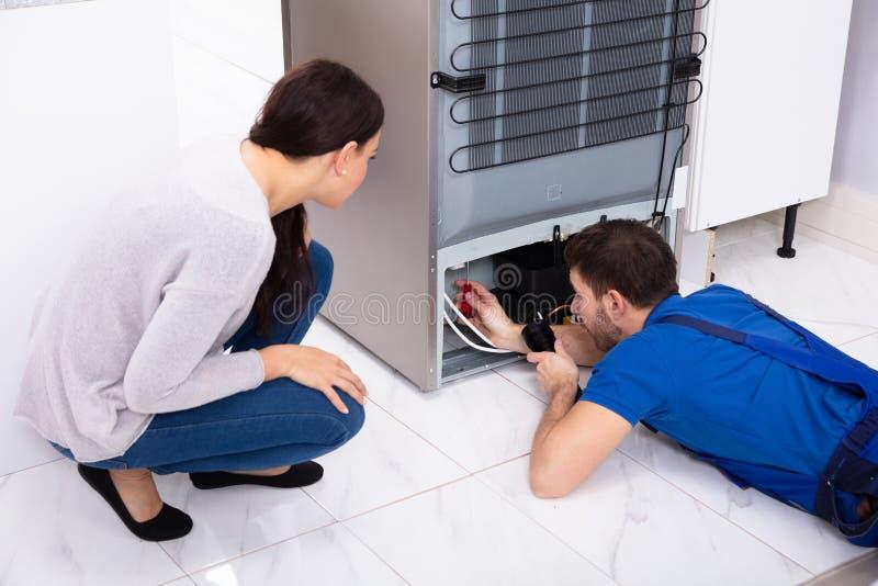 Het Flitslicht van technicusexamining refrigerator with stock fotografie