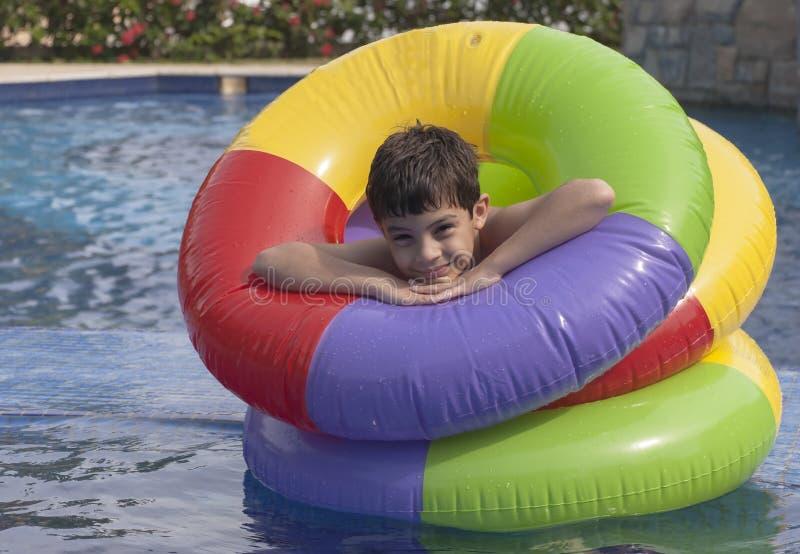 Het floting van de jongen in een pool stock afbeelding