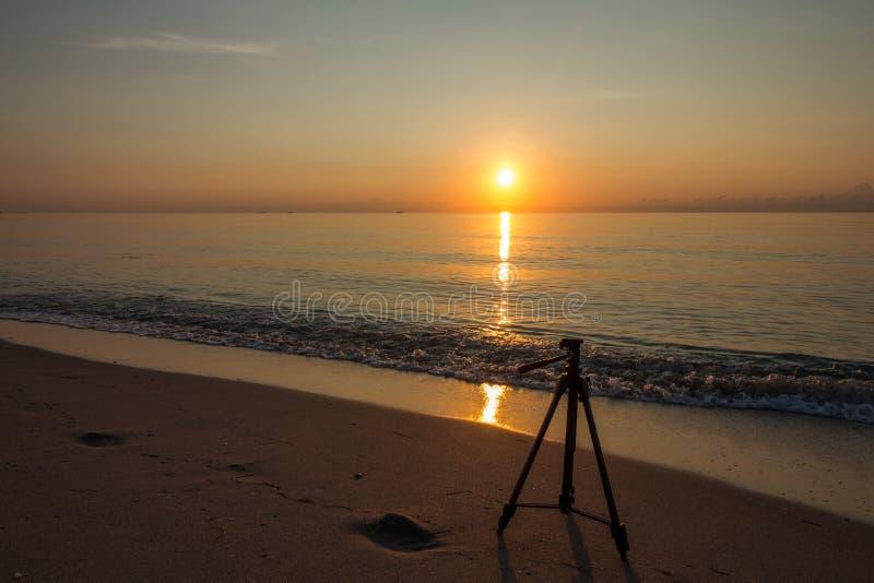 Het fotograferen van zonsopgang in het strand met driepoot stock afbeelding