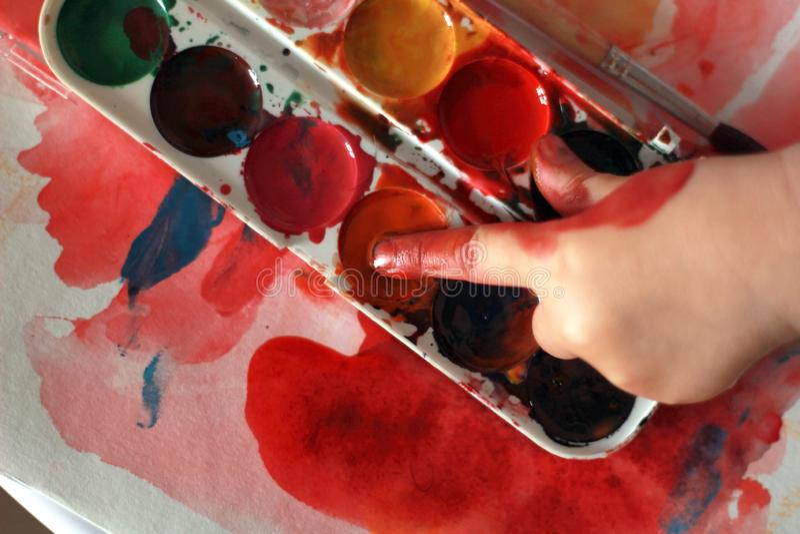 Het fotokind trekt aanrakingen de vinger met de verf van de waterverfhoning royalty-vrije stock foto