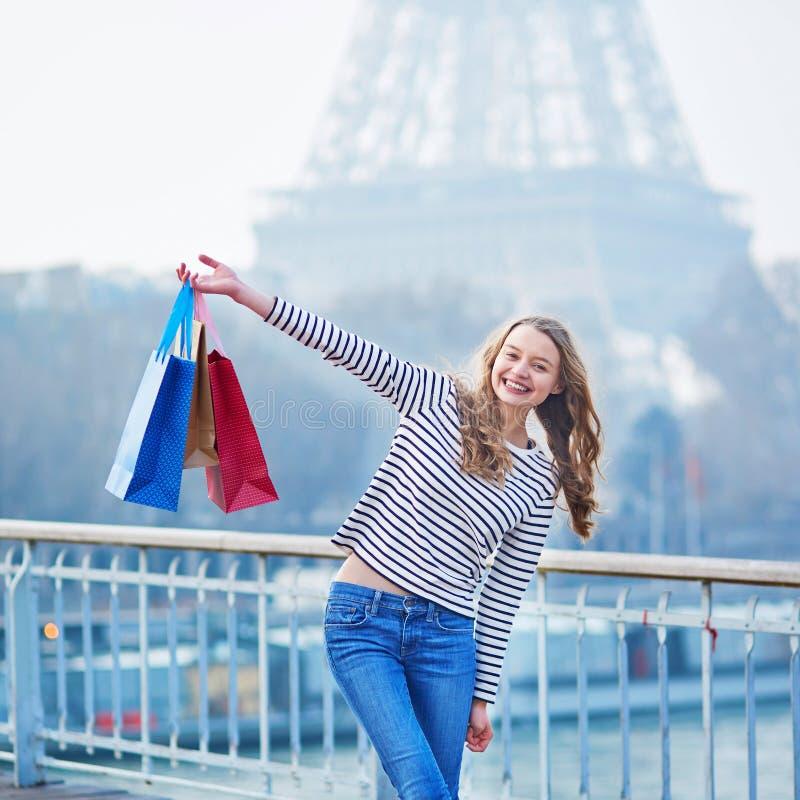 Het Franse meisje met het winkelen doet dichtbij de toren van Eiffel in Parijs in zakken royalty-vrije stock afbeeldingen
