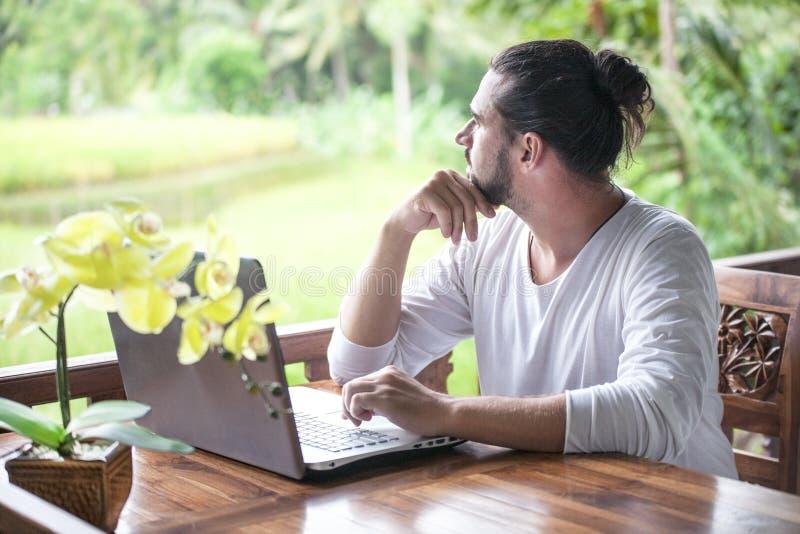 Het freelance werk aangaande laptop Mensenzitting bij houten bureau binnen tuin die aan computer werken royalty-vrije stock foto's