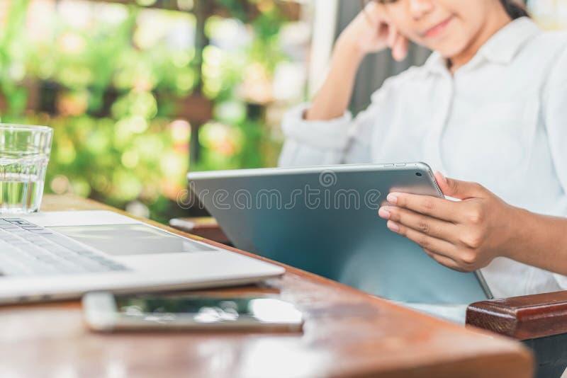 Het freelance werk Toevallige geklede mensenzitting bij houten bureau binnen tuin die aan computer werken die met elektronische k royalty-vrije stock foto's