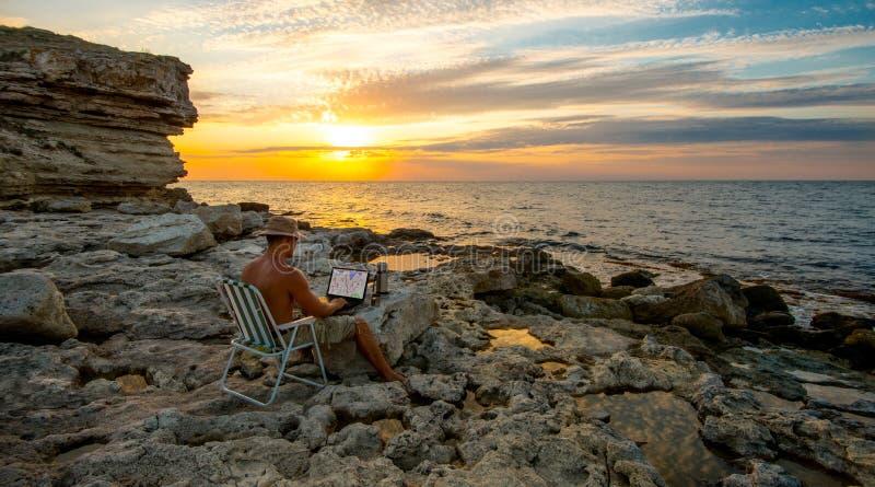 Het Freelancerwerk aangaande laptop op kustoverzees op deauty zonsondergangbackgrou royalty-vrije stock afbeelding