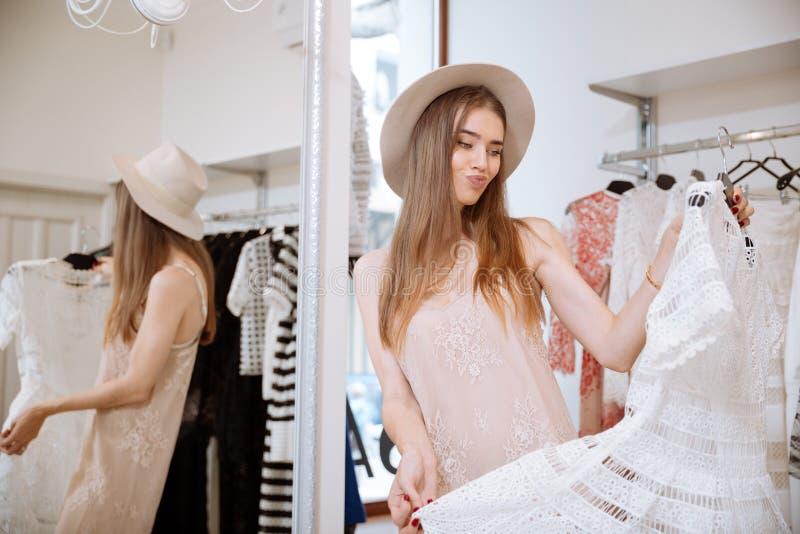 Het fronsen vrouw het doen winkelend en kiezend kleding in kledingsopslag royalty-vrije stock afbeeldingen