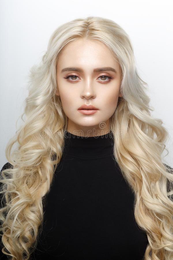 Het frontale portret van een leuk blondemeisje, met gevoelig maakt omhoog, krullend glanzend lang die haar, van een witte achterg stock afbeeldingen