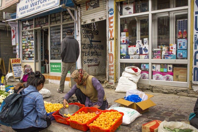 Het fruit en de plantaardige voedselmarkt op de straat en een meisje kopen abrikozen stock afbeeldingen