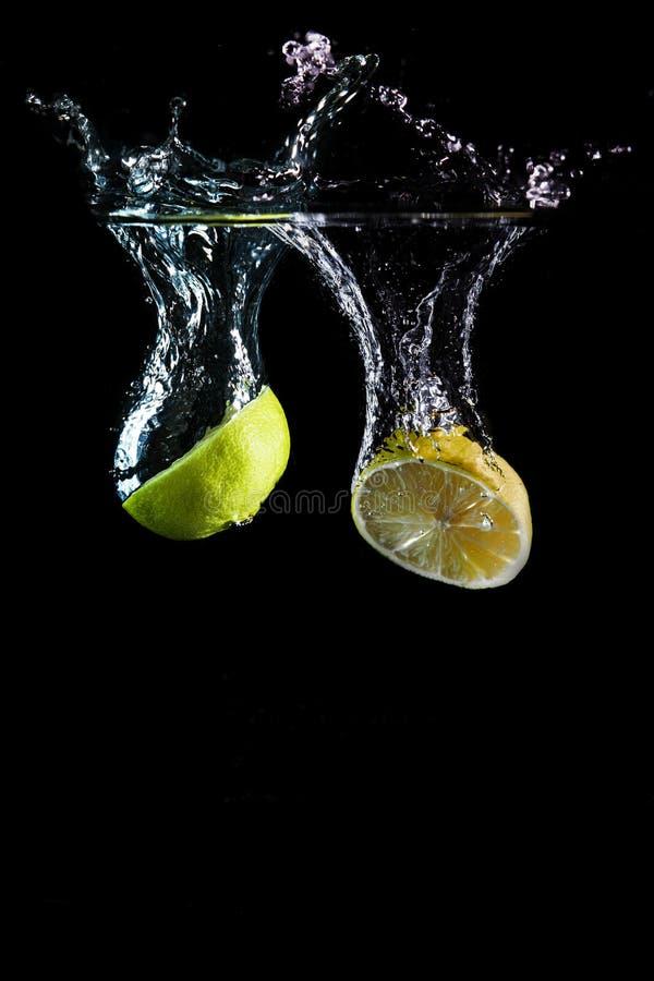 Het fruit van de kalk het dalen in water stock afbeeldingen