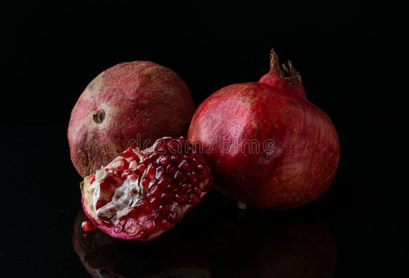 Het fruit van de stillevengranaat Voer op een zwarte achtergrond stock afbeelding