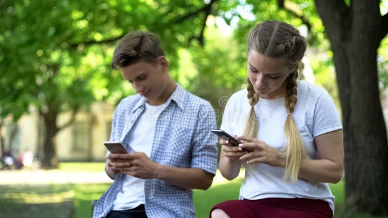 Het gadget wijdde vrienden gebruikend telefoons in park, gebrek aan mededeling, het negeren stock afbeelding