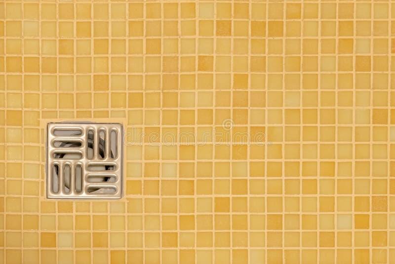 Het gat van het metaalafvoerkanaal in de betegelde vloer van een douche stock afbeelding