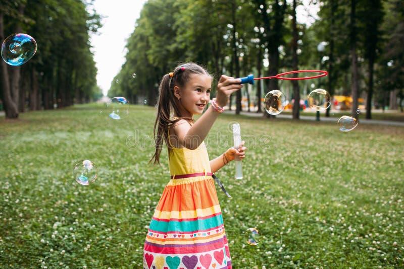 Het geïmponeerde meisje blaast bellen in het park royalty-vrije stock afbeeldingen
