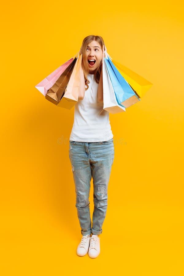 Het geïrriteerde meisje voelt vermoeid van het winkelen, een vrouw met veel zakken, een mooi meisje met zakken op een gele achter stock afbeeldingen