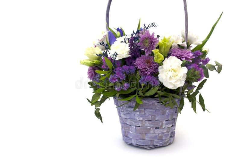 Het geïsoleerde boeket van de lente bloeit in decoratieve rieten houten mand van lilac en purpere bloemen op een witte achtergron royalty-vrije stock foto