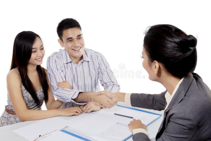 Het geïsoleerde jonge paar ondertekent een contract royalty-vrije stock afbeelding