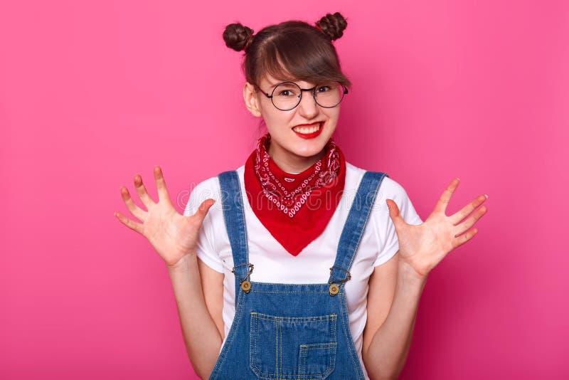 Het geïsoleerde schot van aantrekkelijke donkerbruine mooie tiener, draagt denimoverall, witte toevallige t-shirt, rode bandana d royalty-vrije stock afbeelding