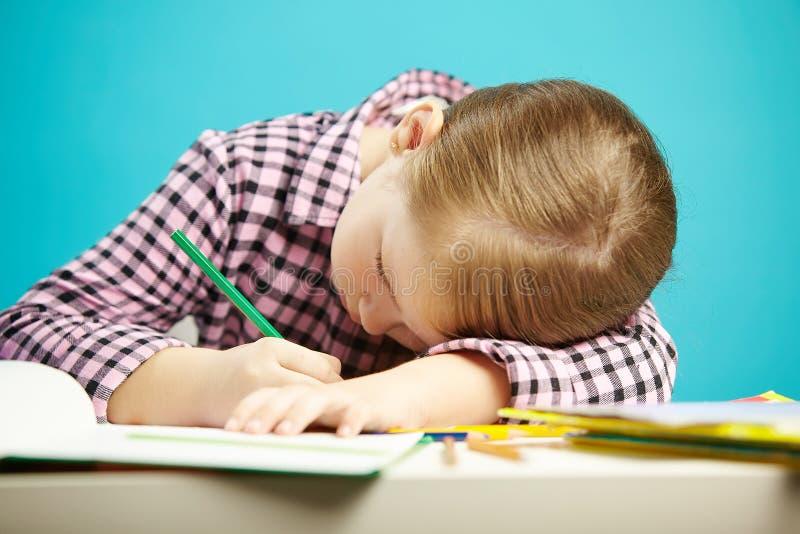 Het geïsoleerde schot van kind met slechte houdingszitting bij bureau en doet thuiswerk Het meisje rustte haar hoofd op lijst en  royalty-vrije stock afbeeldingen