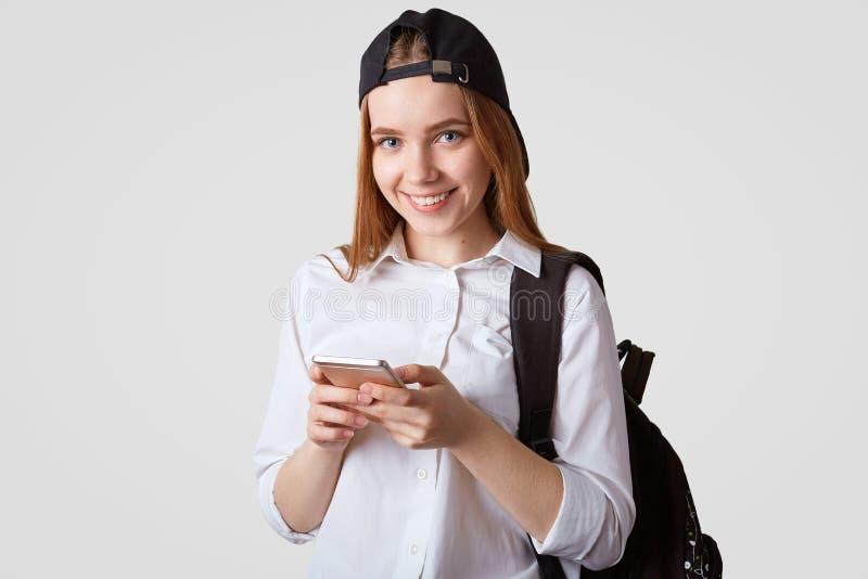 Het geïsoleerde schot van tiener komt van school terug, draagt rugzak, houdt moderne slimme telefoon, surfes sociale online netwe royalty-vrije stock fotografie