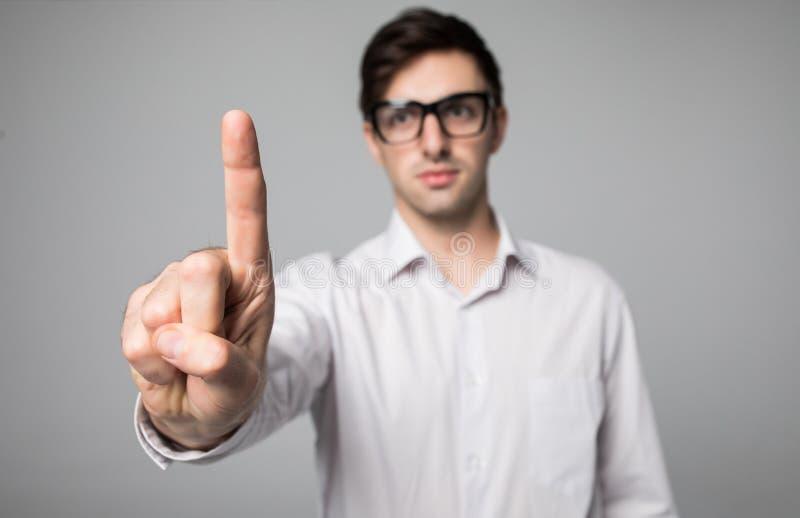 Het gebaar van de mensenwijsvinger, die wit overhemd op grijze achtergrond dragen stock afbeelding