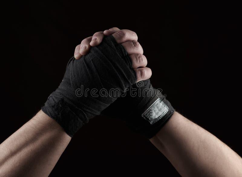 Het gebaar van vriendschap, twee mannelijke handen van een atleet bond met een zwart textielverband royalty-vrije stock fotografie