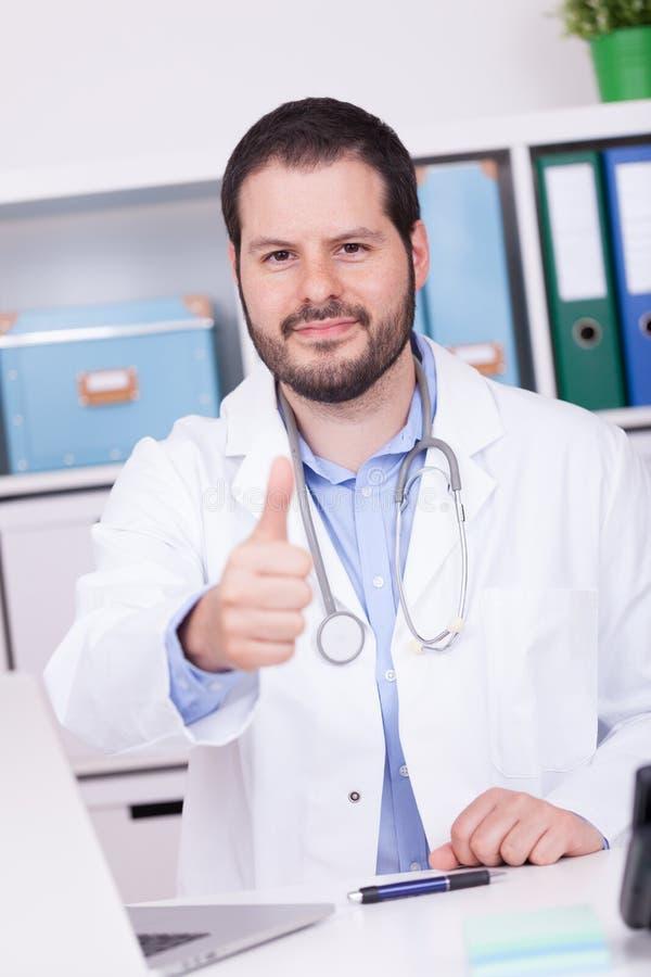 Het gebaarde arts werken bij zijn bureau het tonen beduimelt omhoog Zaken en medisch concept stock fotografie