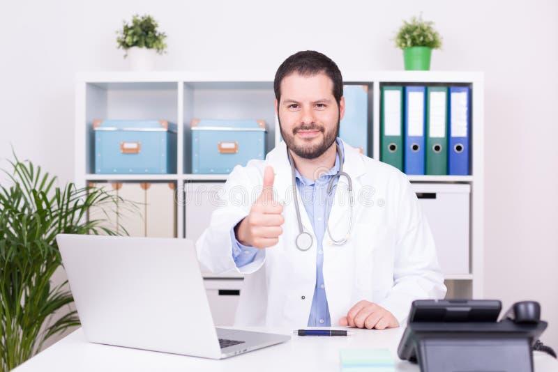 Het gebaarde arts werken bij zijn bureau het tonen beduimelt omhoog Zaken en medisch concept stock foto
