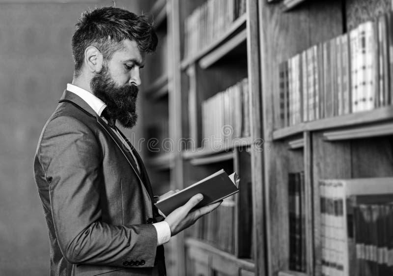 Het gebaarde boek van de mensenlezing in de bibliotheek, mens stock foto's