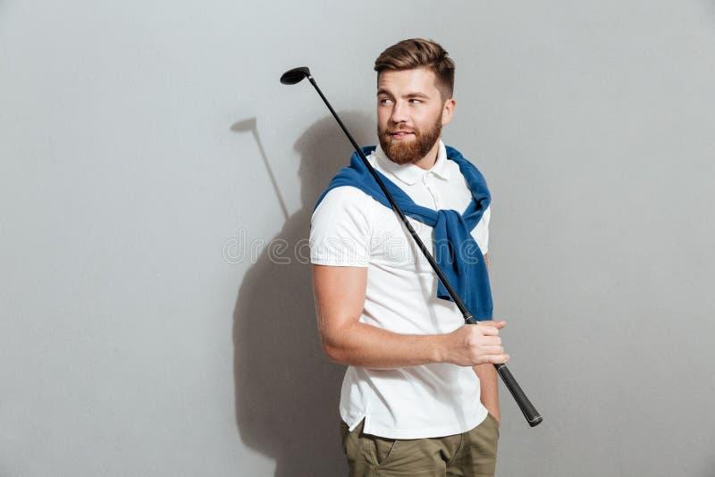 Het gebaarde het Glimlachen golfspeler stellen in studio met in hand club stock afbeelding