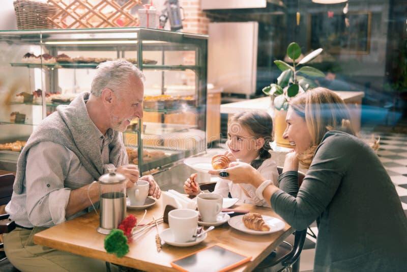 Het gebaarde grijs-haired grootvader glimlachen die zijn leuk aantrekkelijk meisje bekijken royalty-vrije stock afbeelding